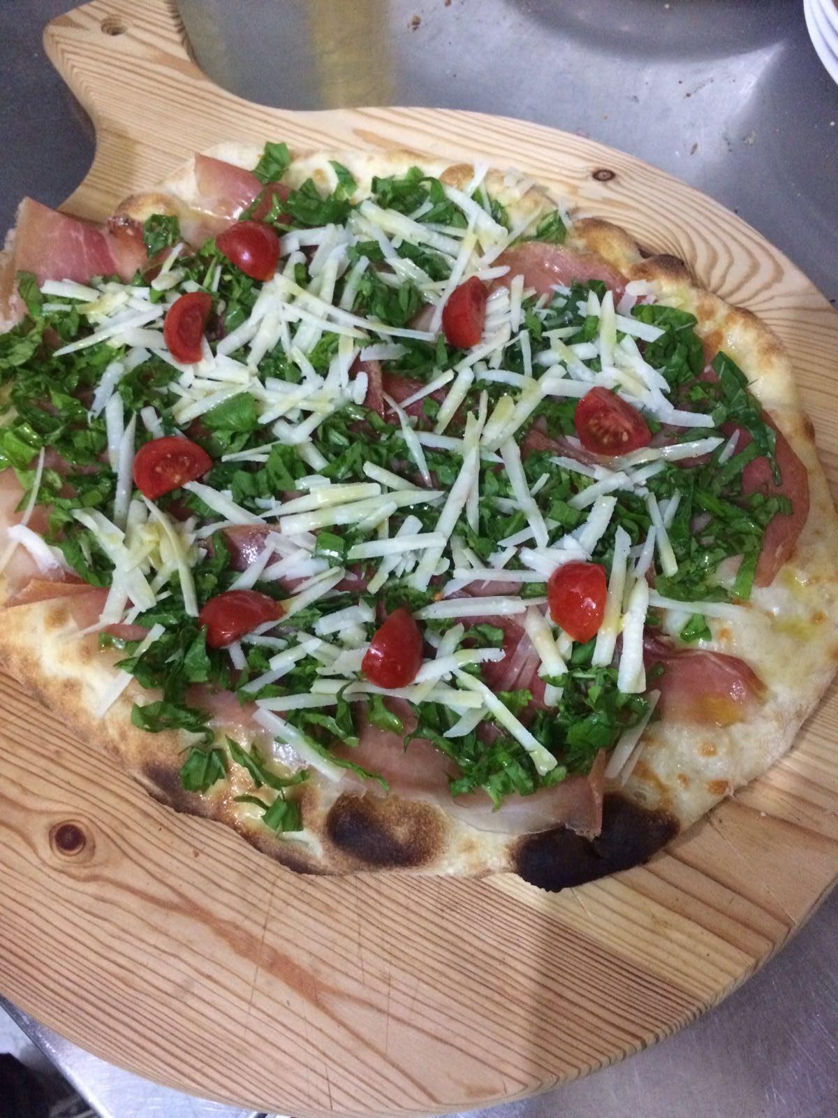 Pizza con prosciutto, rucola, pomodorini e scaglie di parmigiano.